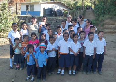 Kelly and Babcock donating $3,000 to school in El Salvador with the students, teacher and Mayita Mendez of Finca Talnamica.